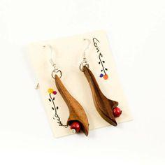 Pendientes en madera de nogal. En madera maciza y bolita roja tambien en madera. Acabado con barniz. Soporte en plata de ley y topes de silicona