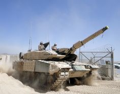 A column of Canadian tanks emerging from the desert, trundling into a NATO airfield in Afghanistan
