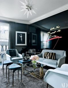 An Art Deco–style rock-crystal chandelier by Alexandre Vossion crowns the smoking room of a Manhattan townhouse by William T. Georgis, where walls painted in a high-gloss Benjamin Moore black are the backdrop for a Marilyn Minter photograph and a neon work by Tracey Emin; the curtains are of a Larsen fabric, and the Carlo Mollino stools, covered in a J. Robert Scott faux suede, are from Salon 94.