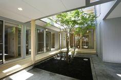 [コート シンボルツリー 建物の中心にコート(中庭)を設ける事で完全に分離しつつもお互いの気配を感じながら生活が可能な空間計画としました。格子戸の開閉により周囲からの適度なプライバシーを確保しつつ内部で開放的な空間となりながらもお互いの世帯が適度な距離感を持ちつつコミュニケーションが計れる家として計画しました。image]