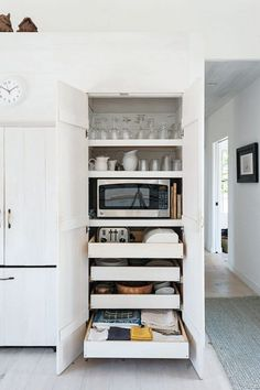 DIY Kitchen Remodel/Inspiration Idea --I love the hidden storage inside of this kitchen cabinet! Use pull out drawers to keep kitchen linens, extra plates, and even small appliances tucked away and out of sight. I love that the microwave is hidden behind the cabinet doors, too!