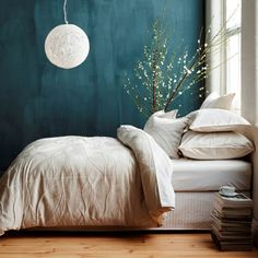 white bed + green blue colored wall