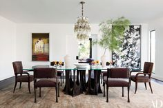 The dining room table is by Paul Evans, as are the four sculpted-metal chairs covered in a Pollack mohair; Émile-Jacques Ruhlmann rosewood armchairs in a Larsen fabric from Cowtan & Tout stand at either end. The vintage light fixture is by Venini, the artworks are by Mike Kelley (left) and Walead Beshty, and the carpet is by Mansour Modern.
