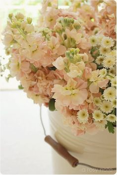 pastel pink (looks like stock) and soft white accent flowers in a vintage pail