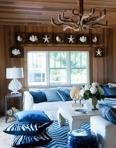 Cedar-plank walls, more shells, a driftwood chandelier, and lots of blue give the pool house both a woodsy and beachy chic.
