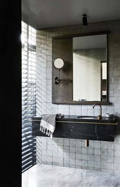 Sleek, modern black and white bathroom with a dramatic black marble floating sink and brass hardware.