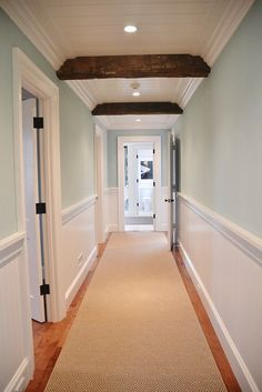 This is almost like beadboard. Such a different feel, maybe a little to country HGTV Dream Home Sherwin Williams Watery in this stunning hallway with white wainscoting and wood beams. Dark Hallway, Long Hallway, Upstairs Hallway, Hallway Paint Colors, Hallway Colours, Paint Colours, Neutral Hallway Paint, Wainscoting Hallway, Wainscoting Styles