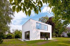 Ein kleiner weißer Kubus, der aus dem Boden zu wachsen scheint. | Neutard Schneider Architekten © Wolfgang Pulfer