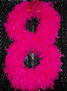 A number cut out of cardboard and wrapped with boas. Perfect for a birthday party! Doing this for Alexi :)