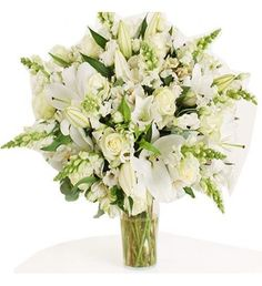 This arrangement contains the following flowers: 10 x White Antirrhinum 15 x Dutch White Roses 10 x White Lisianthus 8 x White Oriental Lilies 12 x White Alstroemeria 2 x Bunches of Eucalyptus - Please note the vase is not included.