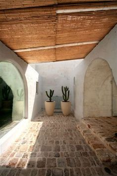 Two tall potted cactus stand outside a clay home and stone floor with a beautiful half-moon window. This is a bold demonstration of how house plants can contribute to your interior design. Patio Interior, Interior And Exterior, Kitchen Interior, Hotel Am Meer, Spanish Style, Beautiful Space, Exterior Design, Interior Architecture, Outdoor Living