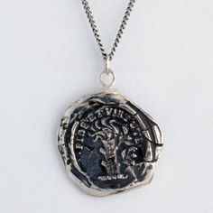 New Path Wax Seal Necklace represents a soul reawakened with newfound direction. Pictured is a tree stump with budding growth, the emblem of renewal and rebirth. Inscribed are the words Fidelity and Virtue, reminding us to stay true to our principles.