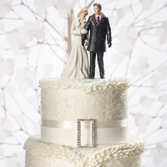 Winter wonderland wedding couple figurine on top of a white cake with diamond accents.