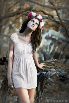 Fairy style display of girl with flower band in her brown hair dressed in white dress