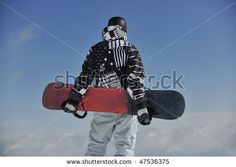 snowboarder relaxing and posing at sunny day on winter season with blue sky in background by dotshock, via ShutterStock