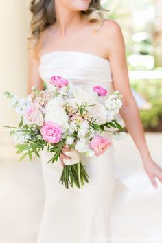 traditional and slightly loose bridal bouquet of white o'hara garden rose, white ranunculus, light pink ranunculus, peach stock, white stock, vendela rose, sophie rose,white sweet pea and elm greenery.