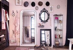 Pared con tres espejos, estante, vitrina y ganchos para accesorios de IKEA.