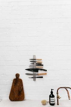 White painted brick wall, DIY copper piping kitchen faucet, and vertical magnetic knife rack at Rye London, a Scandinavian kitchen designed as a photo studio and event space