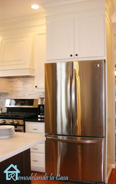 Kitchen Makeover with DIY fridge enclosure and range hood. Painted the cabinets.