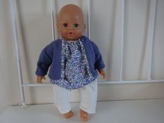 Une jolie tenue coordonnée pour une poupée de 42cm qui comprend : * un pantalon écru lamé doré, * une blouse liberty meadow parme avec une encolure écrue lamé doré (assor - 16644114