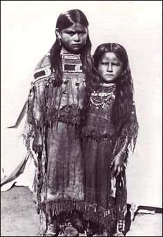 Two young Comanche girls from Oklahoma photographed in decorated Buckskin Dresses, 1891.