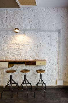 home bar? textured wall is a good way to go to make a part of the open space look different with the same white wall
