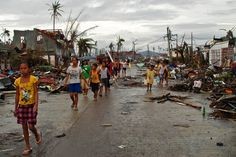 Survivors walk the corridors of the destroyed city of Guiuan on 10 November, where over 23,000 homes were destroyed by a storm that is thought to have killed over 10,000 people, Philippines, 2013, photograph by AP (photographer unattributed).