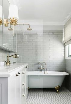 This bathroom features pale grey long subway tiles with a freestanding claw-foot bathtu and brass tapware. Bathroom Styling, Small Bathroom, Bathroom Interior, Bathroom Decor, Clawfoot, Tile Bathroom, Bathroom Interior Design, New Toilet, Mold In Bathroom
