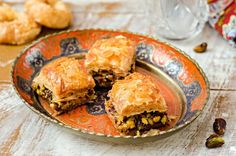 Baklava with pistachios in vintage iron bowl on wooden background by tanchy on @creativemarket