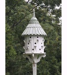Whimsical castle-like purple martin birdhouse with scrolled bracket and tapered shingles