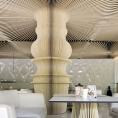 Visually, this column looks like a large paper lantern, making the structure appear much  lighter. Its unity with the ceiling expands out the organic form of the column, growing upward and out in the space.