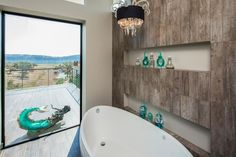 A chic white soaking tub is situated in front of an oversized window in this contemporary bathroom for an unparalleled bathing experience. The window fills the bathroom with natural light while allowing sweeping views of the landscape beyond.