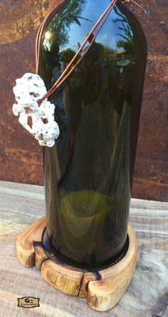 Wine Bottle Candle Holder - Mazzei Badiola Toscana Italian wine. Top edge angled cut, bottom edge double notch for air flow live candle use. Hand-picked Kauai coral on leather cord. Ficus wood base oil finished ridge cut to level bottle placement and candle.