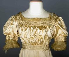 AESTHETIC EVENING GOWN, 1905-1910 Candlelight satin empire trained gown, square neckline, short puff sleeves, bands of stylized cream embroidery, neckline & sleeves w/ gathered silk chiffon trim,