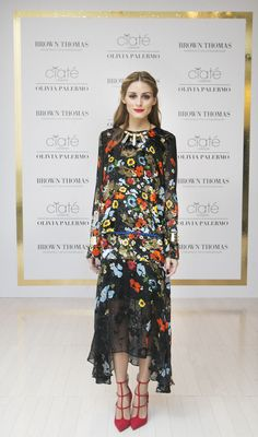 Olivia Palermo wears a Preen floral dress, with jewelry from BaubleBar, and Christian Louboutin red stilettos