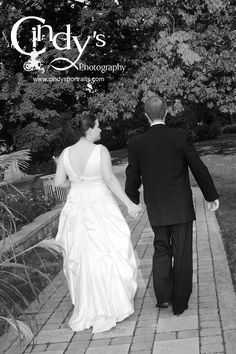 Bride and Groom holding hands taking a walk in the Park of Roses in Columbus, Ohio - Are you or someone you know getting married in  Ohio, check out Cindy's Photography for an experienced and affordable wedding photographer
