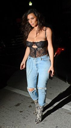 It's 1990 again! The Keeping Up With The Kardashians modeled a rocker look that consisted of a bustier top and ripped jeans with snakeskin boots on Thursday in Miami