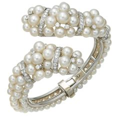 Pearl and Diamond Cuff ~~ 18KT white gold, Akoya cultured pearl hinged cross-over bangle bracelet accented with round brilliant cut diamonds weighing approximately 2.50ctsTW.