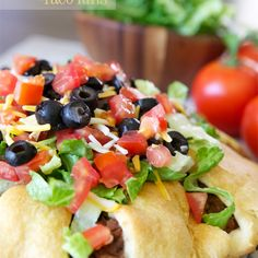 The Pampered Chef Taco Ring Recipe Main Dishes with crescent rolls, hamburger, refried beans, taco seasoning, tomatoes, lettuce, sour cream, olives, salsa, shredded cheddar cheese