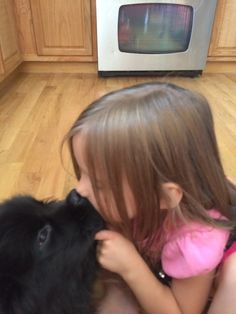 Puppy love! She loves her Newfie pup!