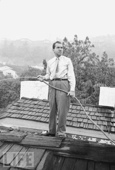 """January 9, 1913: Richard Nixon is born. Here, Nixon wets the wood-shingled roof of his rental house during a Los Angeles fire in 1961. """"Never let your head hang down,"""" he said. """"Never give up and sit down and grieve. Find another way. And don't pray when it rains if you don't pray when the sun shines."""" Click the image to see more of The Nixon You Never Knew."""