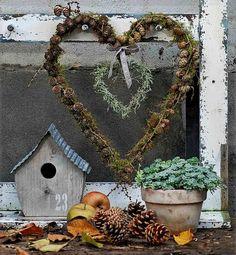 """Gentagelser er et af de kneb, Bettina Weisbrod benytter sig af. Her i form af et """"hjerte i hjertet"""". Begge er bundet på en købt hjerteform, men du kan også selv bøje hjerter med tyk elefanttråd. Det store hjerte er først omvundet med skovmos, og derpå er der bundet lærkegrene med kogler fast med tynd sølvtråd. Det lille hjerte er bundet med hekselyng og sat fast under det store med et stykke metaltråd. Hjerterne er hængt på en gammel, afskallet træramme, og tableauet er fuldendt med et…"""