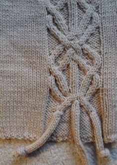 Dress up your work with decorative knitting stitches.  Close Up on Cable Knit Stitch in Grey Garment