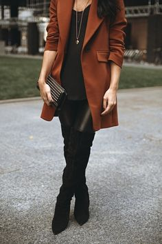 rust brown orange coat + black shirt + suede over the knee black boots + leather pants + clutch
