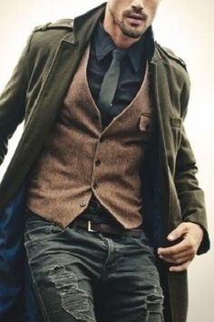Great layering look - brown tweed waistcoat and military overcoat worn over a dark shirt and tie, and jeans.