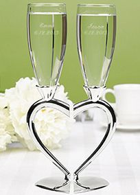 """Your lives and hearts are entwined beautifully so symbolize it by toasting with these unique flutes! The silver-plated stems allow the flutes to stand alone elegantly and fit together to form the shape of a complete heart. Flutes stand 10 1/2"""" tall and may be personalized in your choice of font with two lines of personalization such as bride's name and wedding date on one flute and groom's name and wedding date on the other flute. Personalization will allow for up to 25 characters per line…"""