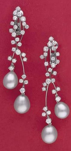 A Pair of Cultured Pearl and Diamond Earrings  Each circular-cut diamond cluster surmount suspending two sweeping knife-edge fringes assymetrically decorated with circular-cut diamonds, terminating in two cultured pearl drops, mounted in 18K white gold, length 8.0 cm.
