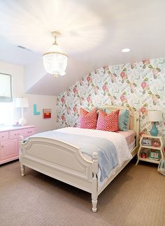 Pink and blue girl's bedroom with pink and blue floral wallpaper accent wall framing white poster bed filled with blue ruffled shams, pink diamonds pillow and blue blanket flanked by turquoise blue lamp on Serena & Lily Curvee Shelf Table.