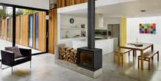 9 Wood Stove Fireplaces That Are Stoking Our Flames , modern minimal living room and dining room with wood stove fireplace. Home Fireplace, Fireplace Design, Contemporary Kitchen Design, Interior Design Kitchen, Double Sided Fireplace, Double Sided Stove, Long House, House 2, Casa Patio