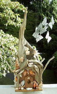 Fairy house made from interesting twisty driftwood and some very cool sea shells by Sweet2Spicy, via Flickr